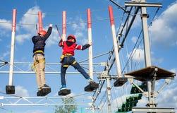 享受活动的孩子在一个上升的冒险公园在一个晴天 免版税库存照片