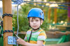 享受活动的小逗人喜爱的男孩在一个上升的冒险公园在一个夏天晴天 上升在绳索操场struct的小孩 免版税库存照片