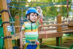 享受活动的小逗人喜爱的男孩在一个上升的冒险公园在一个夏天晴天 上升在绳索操场struct的小孩 库存图片