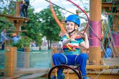 享受活动的小逗人喜爱的男孩在一个上升的冒险公园在一个夏天晴天 上升在绳索操场struct的小孩 免版税库存图片