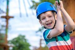 享受活动的小逗人喜爱的男孩在一个上升的冒险公园在一个夏天晴天 上升在绳索操场struct的小孩 图库摄影