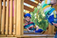 享受活动的小逗人喜爱的男孩在一个上升的冒险公园在一个夏天晴天 上升在绳索操场struct的小孩 库存照片