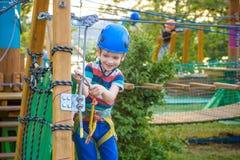 享受活动的小逗人喜爱的男孩在一个上升的冒险公园o 图库摄影