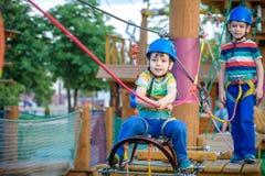 享受活动的小逗人喜爱的男孩在一个上升的冒险公园o 免版税库存图片