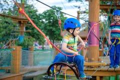 享受活动的小逗人喜爱的男孩在一个上升的冒险公园o 免版税库存照片
