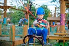 享受活动的小逗人喜爱的男孩在一个上升的冒险公园o 库存照片