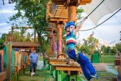 享受活动的小逗人喜爱的男孩在一个上升的冒险公园o 库存图片