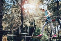 享受活动的愉快的学校女孩在一个上升的冒险公园 图库摄影