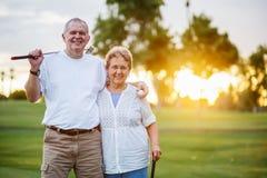 享受活跃生活方式的愉快的资深夫妇画象打高尔夫球 免版税库存图片