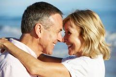 享受浪漫海滩节假日的高级夫妇 免版税库存图片