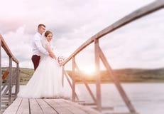 享受浪漫片刻的年轻婚礼夫妇外面在t旁边 免版税图库摄影