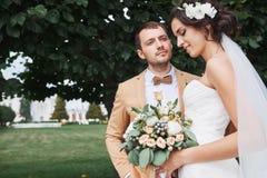 享受浪漫片刻的年轻婚礼夫妇外面 库存图片