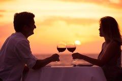 享受浪漫sunnset晚餐的夫妇 免版税库存图片