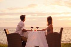 享受浪漫sunnset晚餐的夫妇 免版税库存照片