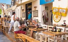享受海岸线的游人在餐馆在法维尼亚纳海岛的中心,是最大三个Aegadian海岛 免版税库存图片