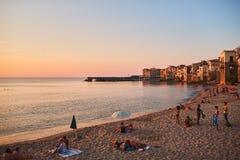 享受海滩和美好的日落的游人 免版税库存照片