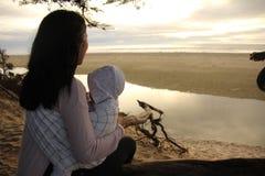 享受海滩日落的母亲和孩子 免版税图库摄影