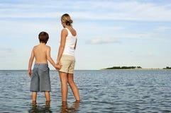 享受海视图的母亲和儿子 免版税库存照片