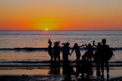 享受海边日落的人们 免版税库存照片