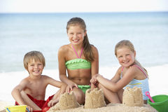 享受海滩假日的小组孩子 免版税图库摄影