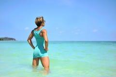 享受海滩放松的愉快的妇女快乐在夏天 库存图片