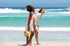享受海滩生活方式的两个赤足朋友 图库摄影