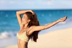 享受海滩自由乐趣的愉快的自由的比基尼泳装妇女 免版税库存照片