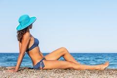 享受温暖的夏日的妇女在海边 免版税库存照片