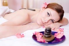 享受温泉放松:获得美丽的年轻可爱的白肤金发的妇女放松在石疗法按摩&芳香疗法期间的乐趣 库存照片