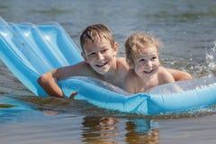 享受游泳与可膨胀的知更鸟蛋蓝色水池空气席子的两个孩子在室外夏天的池塘 图库摄影