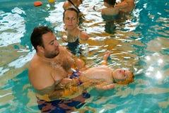 享受游泳在与与他们的亲戚的一个水池的可爱的婴孩 免版税库存图片