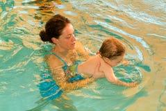 享受游泳在与他的母亲的一个水池的可爱的婴孩 库存照片
