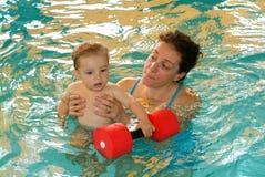 享受游泳在与他的母亲的一个水池的可爱的婴孩 库存图片