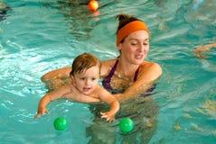享受游泳在与他的母亲的一个水池的可爱的婴孩 免版税库存照片