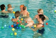 享受游泳在与他的母亲的一个水池的可爱的婴孩 图库摄影