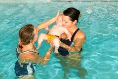 享受游泳在与他的母亲的一个水池的可爱的婴孩 免版税图库摄影