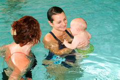 享受游泳在与他的母亲的一个水池的可爱的婴孩 免版税库存图片