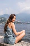 享受湖视图的微笑的女孩 免版税图库摄影