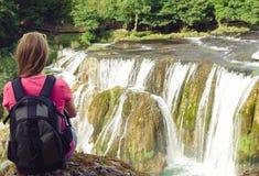 享受瀑布视图的少妇背包徒步旅行者 免版税库存照片