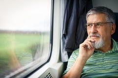享受火车旅行的老人 免版税图库摄影