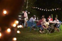享受烤肉晚餐的多一代黑色家庭 免版税库存图片