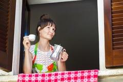 享受热的咖啡饮料的愉快的妇女画象在坐在开窗口附近的意大利moka罐新近地酿造了与 库存图片