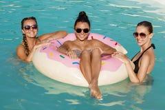 享受热的夏日的朋友在游泳池边 库存照片