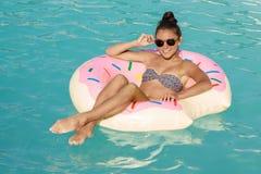 享受热的夏日的美女在游泳池边 免版税图库摄影