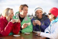 享受热饮料的组朋友在滑雪胜地 免版税库存照片