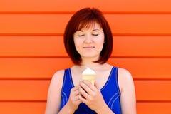 享受片刻:蓝色衬衣身分的年轻女人与接近的眼睛微笑和拿着在手上冰淇凌的 免版税库存图片