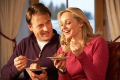 享受片式蛋糕的夫妇坐沙发 免版税库存照片