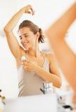 享受生气勃勃的愉快的妇女在应用路辗防臭剂以后 免版税库存图片
