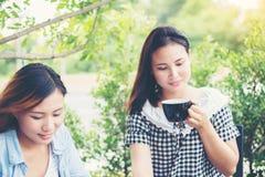 享受的两个朋友面带笑容在咖啡店 库存图片