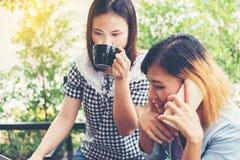 享受的两个朋友面带笑容在咖啡店 库存照片